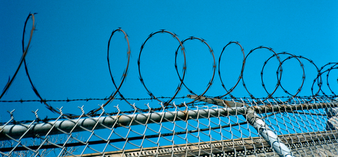 Fence with barbed wire at the top against a clear blue sky.