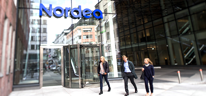 Three persons walking outside a Nordea office.
