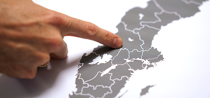 Hand pointing at county map of Sweden.