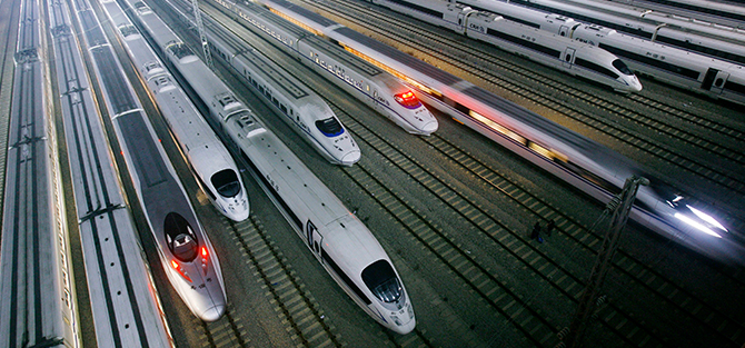 Several high-speed trains are at a large railway station.