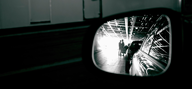 Two silhouettes in a rear view mirror.