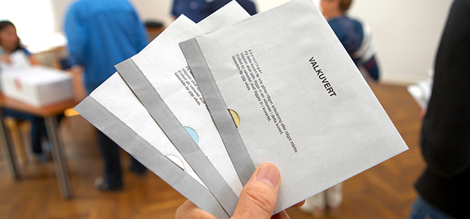 Hand with three ballot envelopes in the polling station.